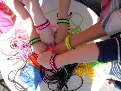 Das Foto zeigt die Arme der Teilnehmerinnen mit den selbst geknoteten Paracord-Armbändern.