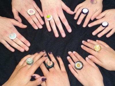 Das Foto zeigt die Hände der Teilnehmerinnen mit den selbst gestalteten Knopfringen.
